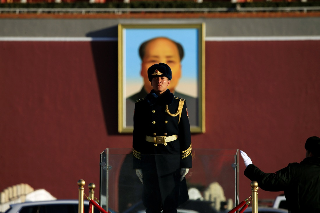 Military officer stands guard in front of a portrait of former Chinese chairman Mao Zedong
