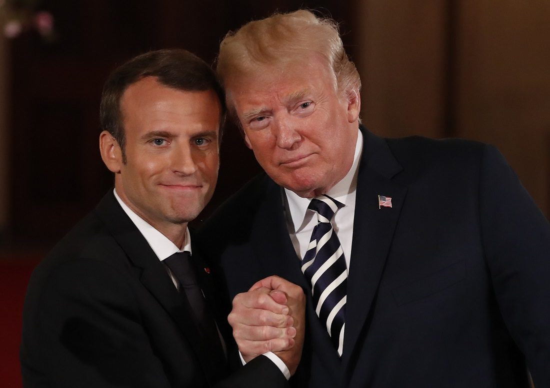 French President Macron clasps hands with U.S. President Trump at the conclusion of their joint news conference at the White House in Washington