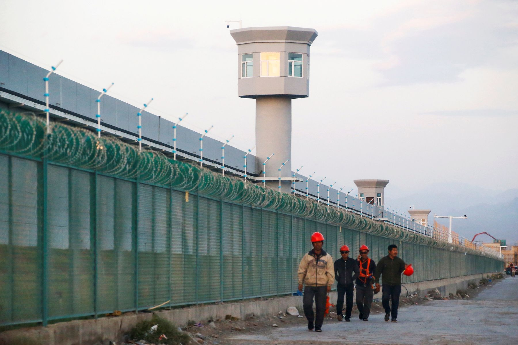 Workers walk by the perimeter fence of what is officially known as a vocational skills education centre in Dabancheng