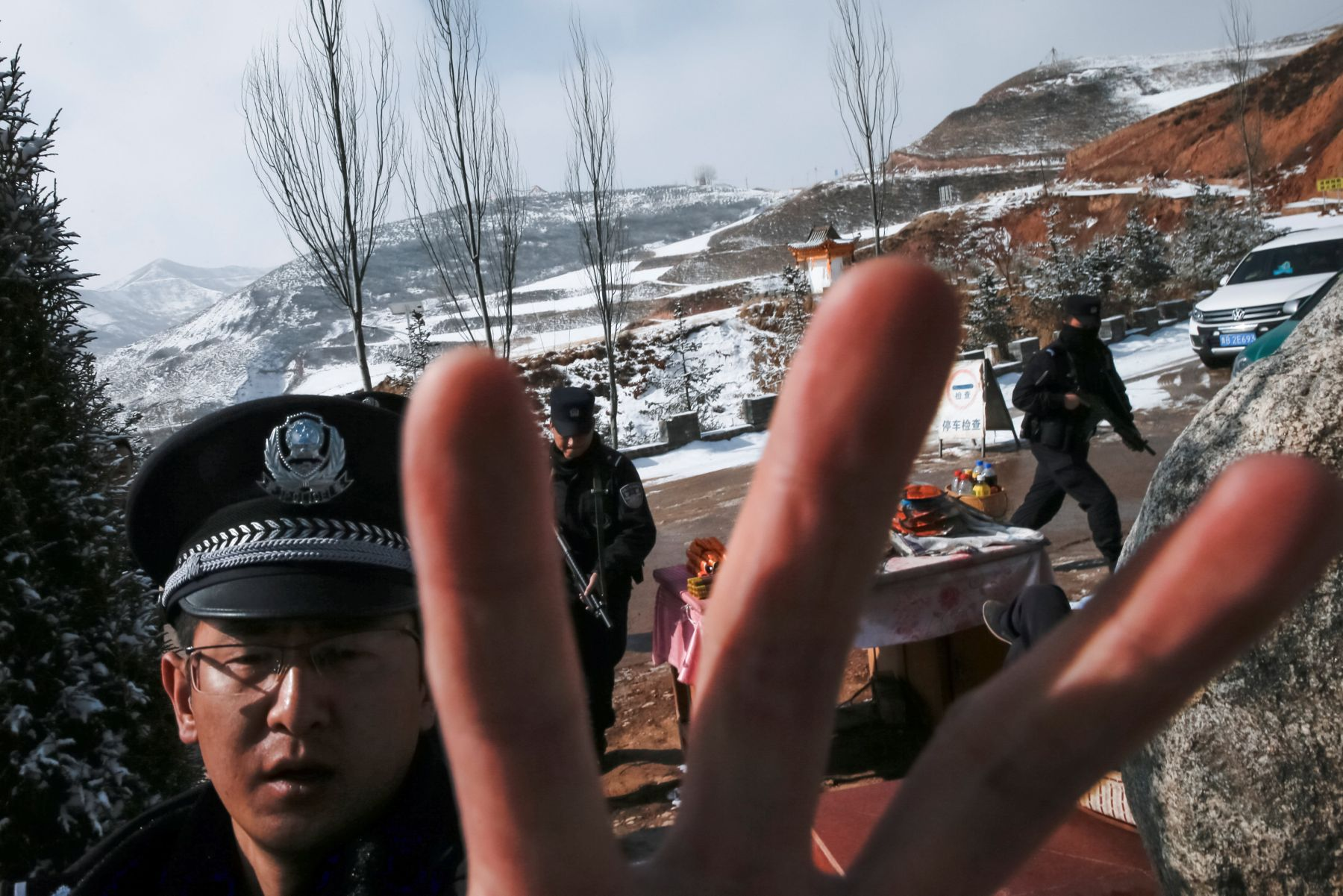Armed police attempt to prevent the taking of pictures at a checkpoint at the entrance to Taktser, the birthplace of the Dalai Lama