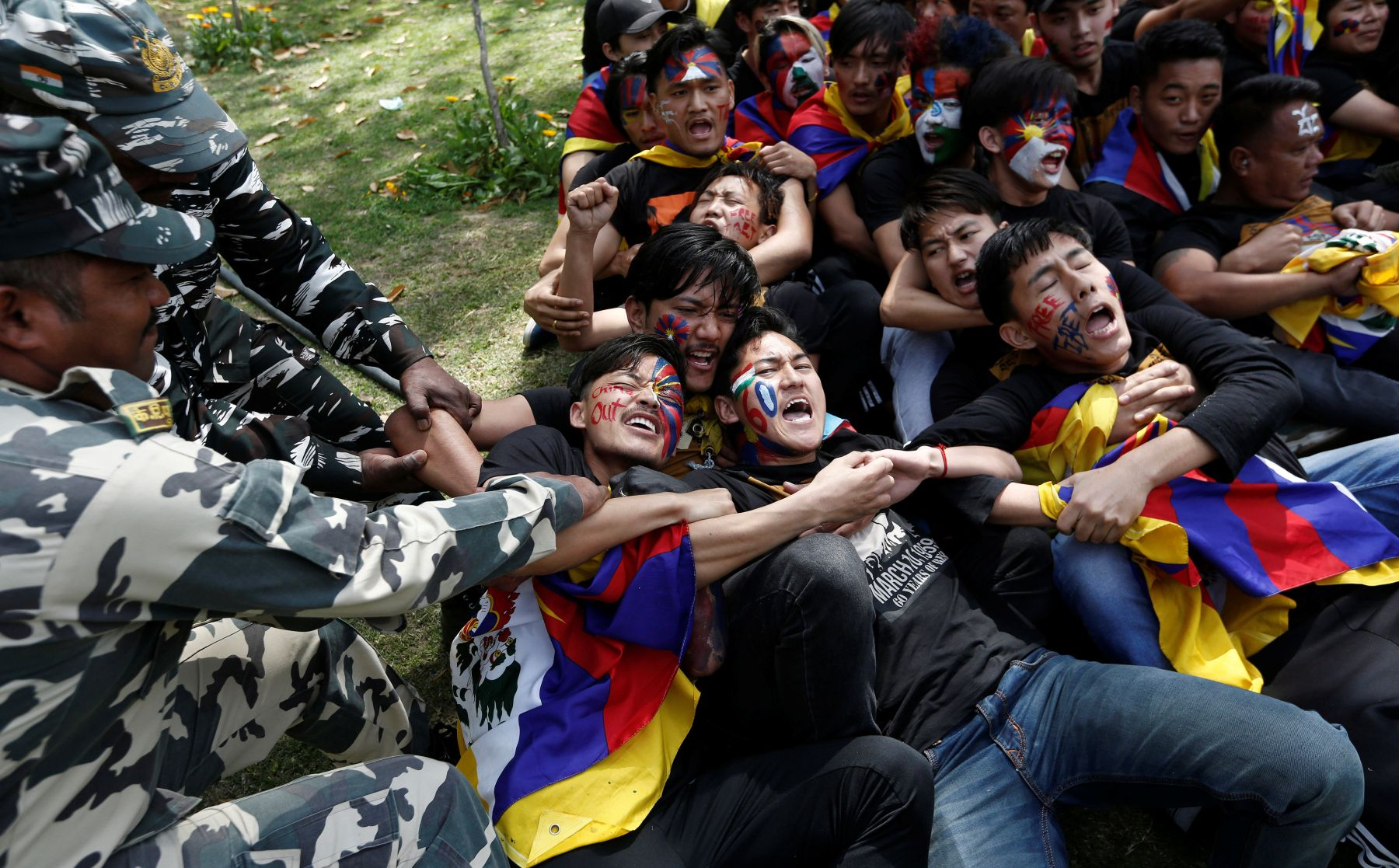 Police officers detain Tibetans during a protest held to mark the 60th anniversary of the Tibetan uprising against Chinese rule, outside Chinese embassy in New Delhi