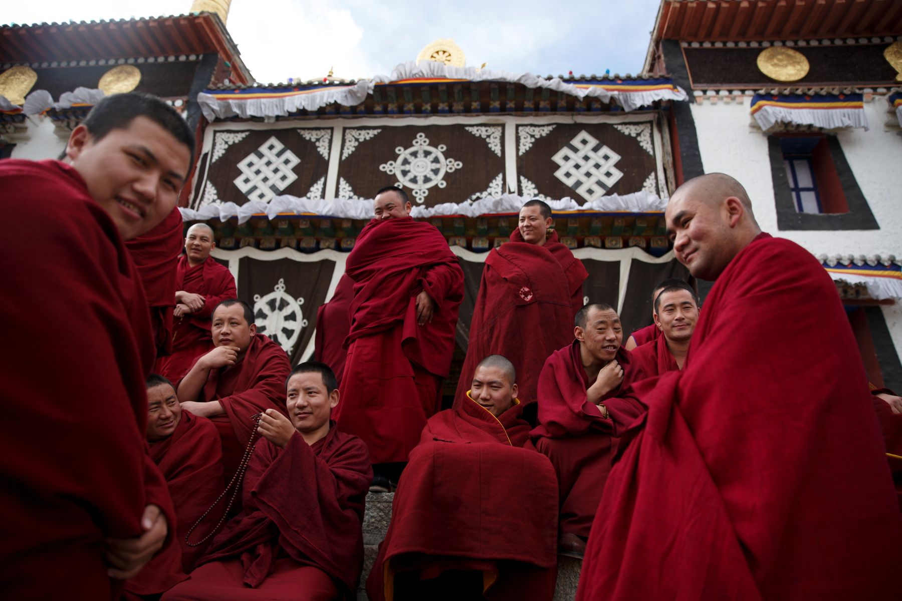 Buddhist monks sit outside a prayer hall at Rongwo Monastery in the largely ethnic Tibetan town of Rebkong