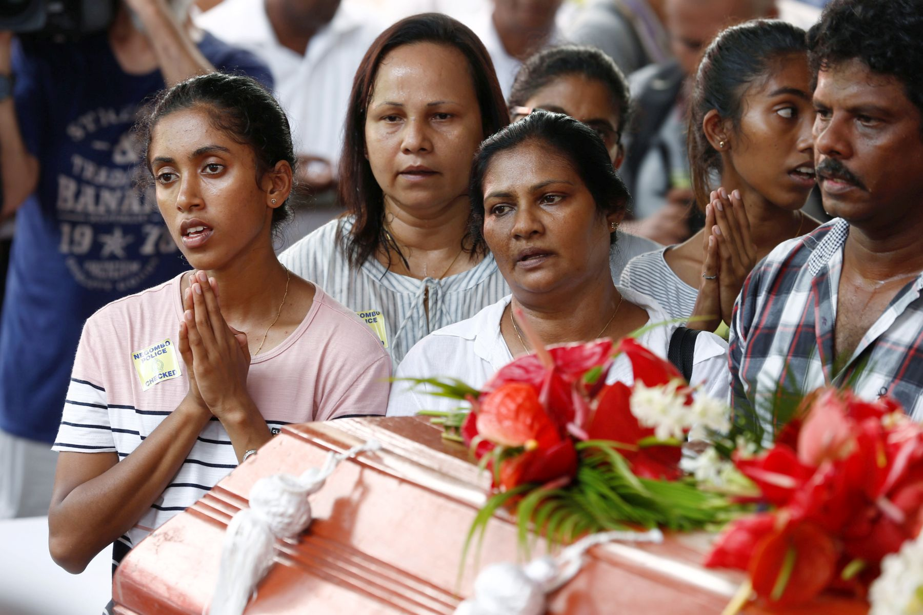 People attend a mass burial of victims at a cemetery near St. Sebastian Church in Negombo