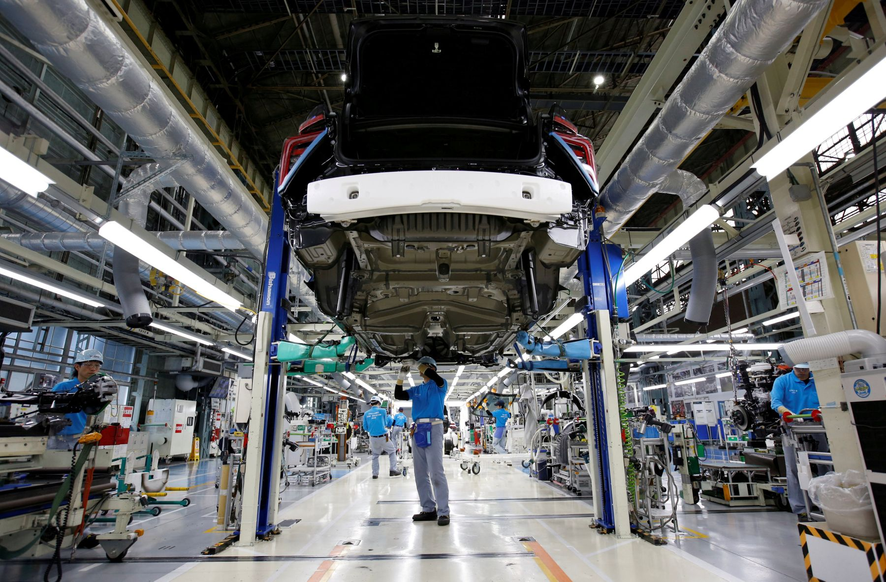 FILE PHOTO: Employees of Toyota Motor Corp. work on assembly line in Toyota