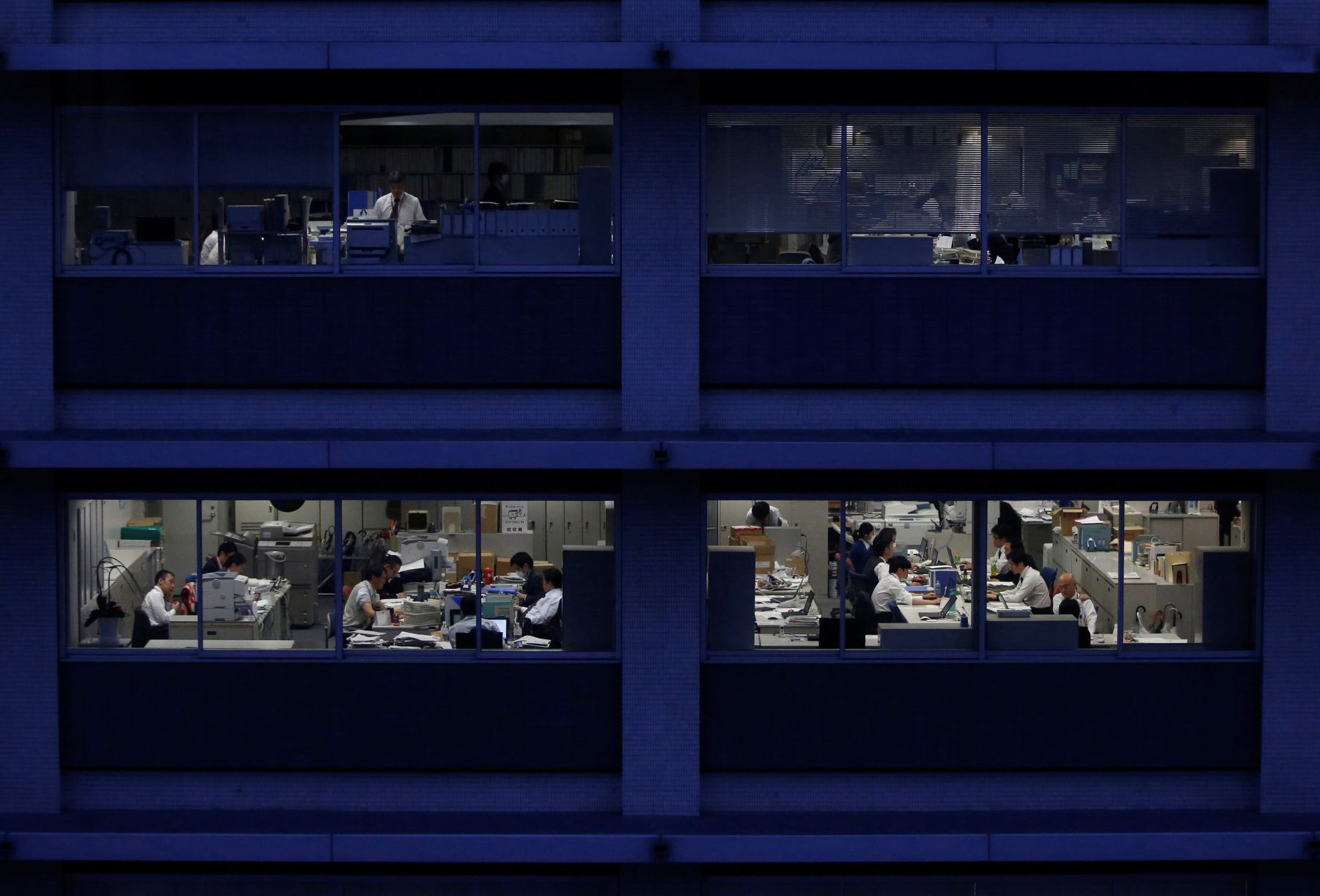 FILE PHOTO: Office workers are pictured through building windows during dusk in Tokyo