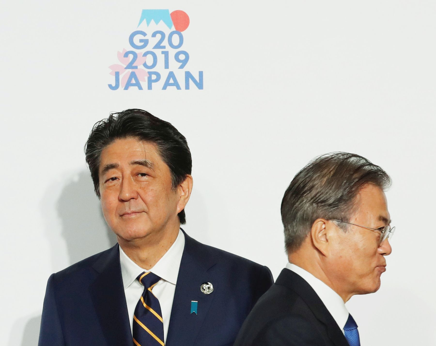 South Korean President Moon Jae-In is welcomed by Japanese Prime Minister Shinzo Abe upon his arrival for a welcome and family photo session at G20 leaders summit in Osak