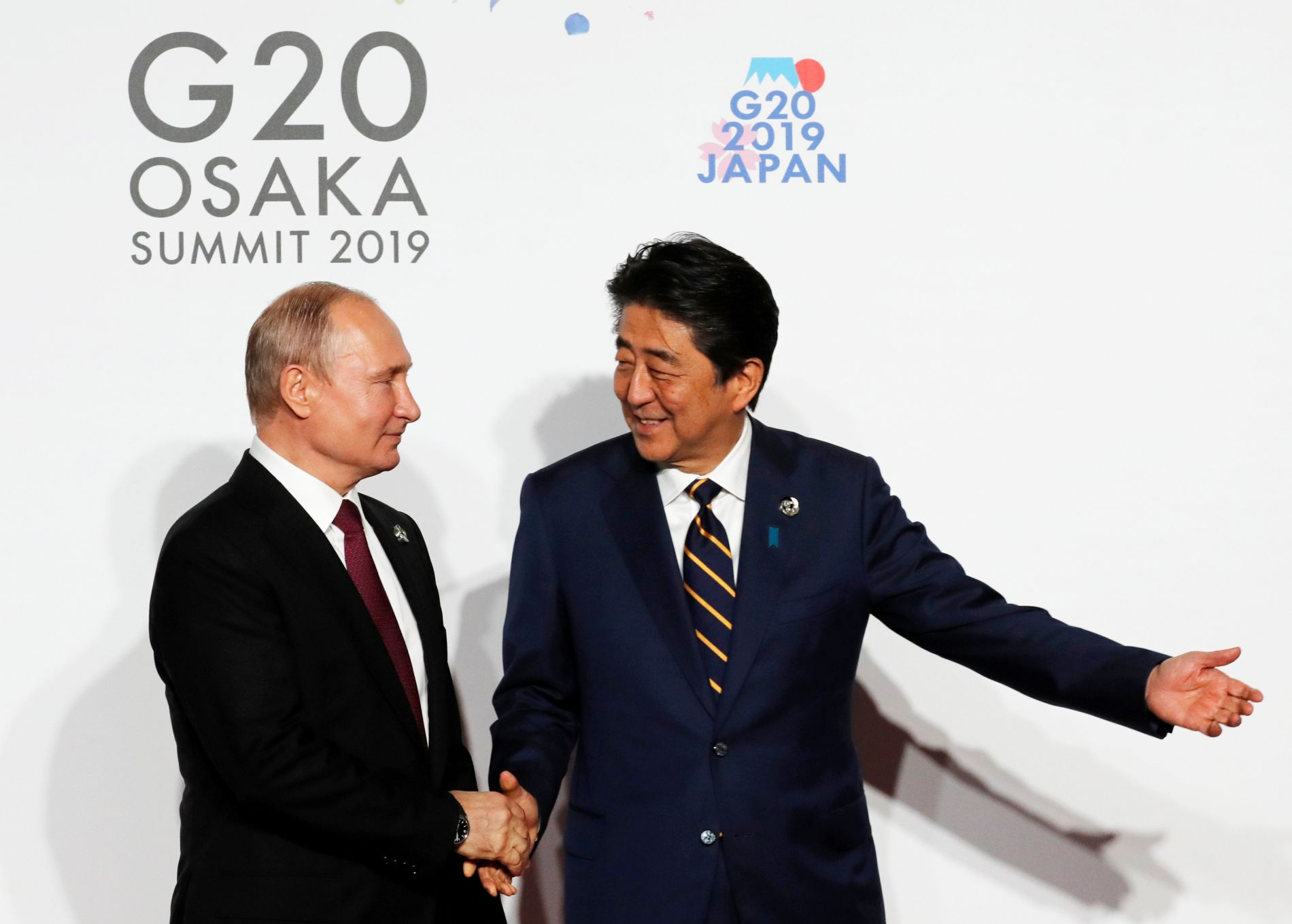 Russian President Vladimir Putin is welcomed by Japanese Prime Minister Shinzo Abe upon his arrival for a welcome and family photo session at G20 leaders summit in Osaka