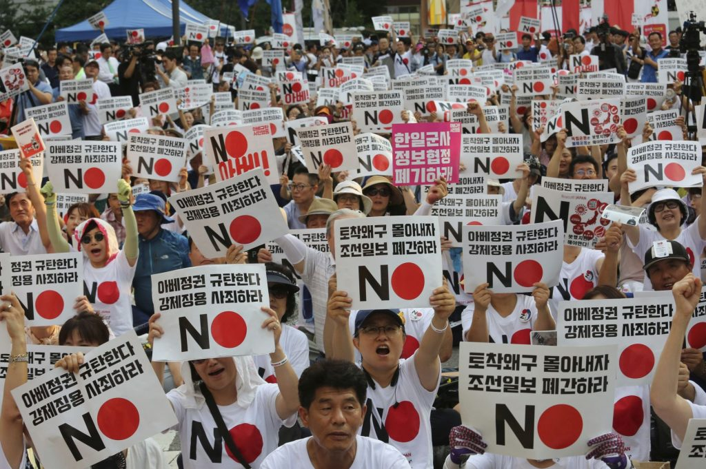 """South Korean protesters stage a rally to denounce Japan's new trade restrictions on South Korea in front of the Japanese embassy in Seoul, South Korea, Saturday, Aug. 3, 2019. Japan's Cabinet on Friday approved the removal of South Korea from a list of countries with preferential trade status, prompting retaliation from Seoul where a senior official summoned the Japanese ambassador and told him that South Koreans may no longer consider Japan a friendly nation. The placards read: """"We denounce Japanese Prime Minister Shinzo Abe."""" (AP Photo/Ahn Young-joon)"""