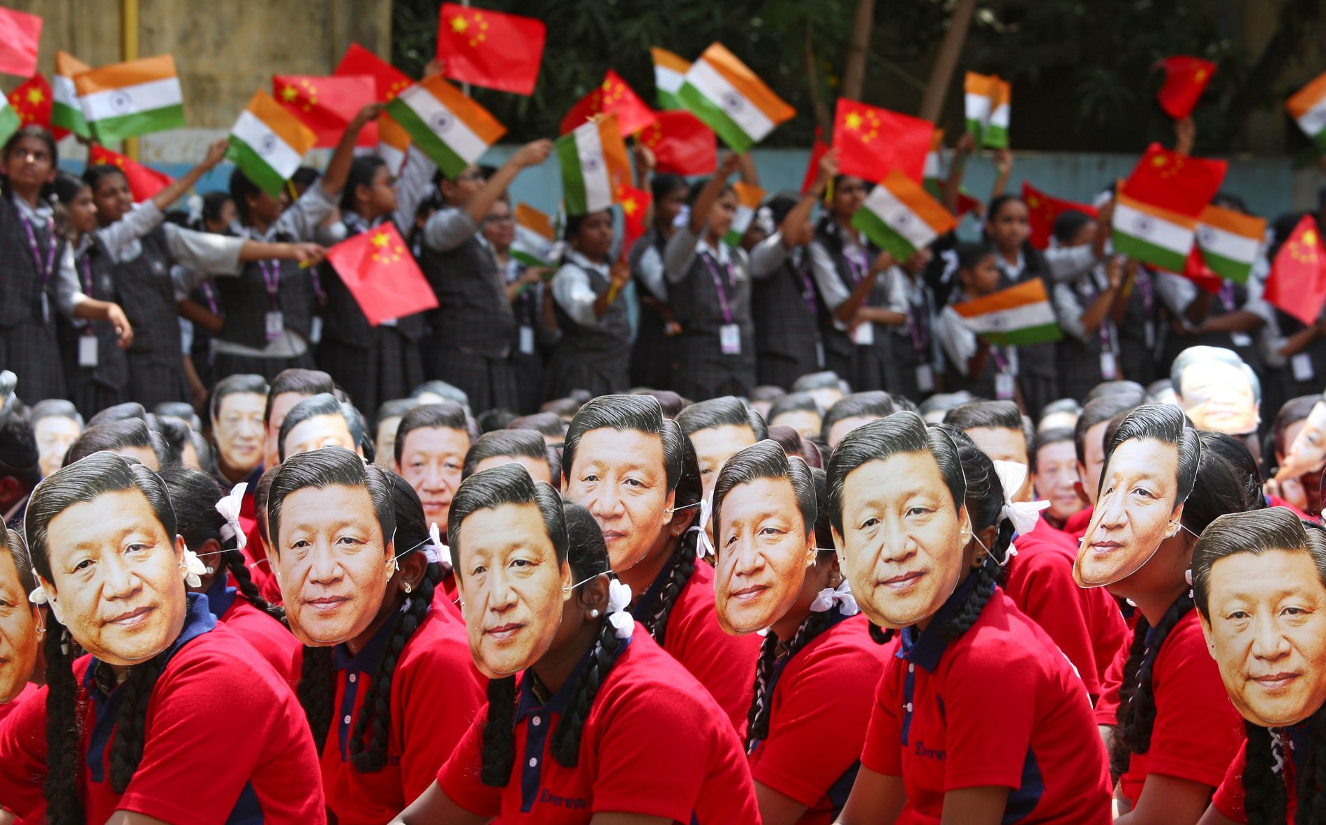 Students wear masks of China's President Xi Jinping as other waves national flags of India and China, ahead of the informal summit with India's Prime Minister Narendra Modi, at a school in Chennai