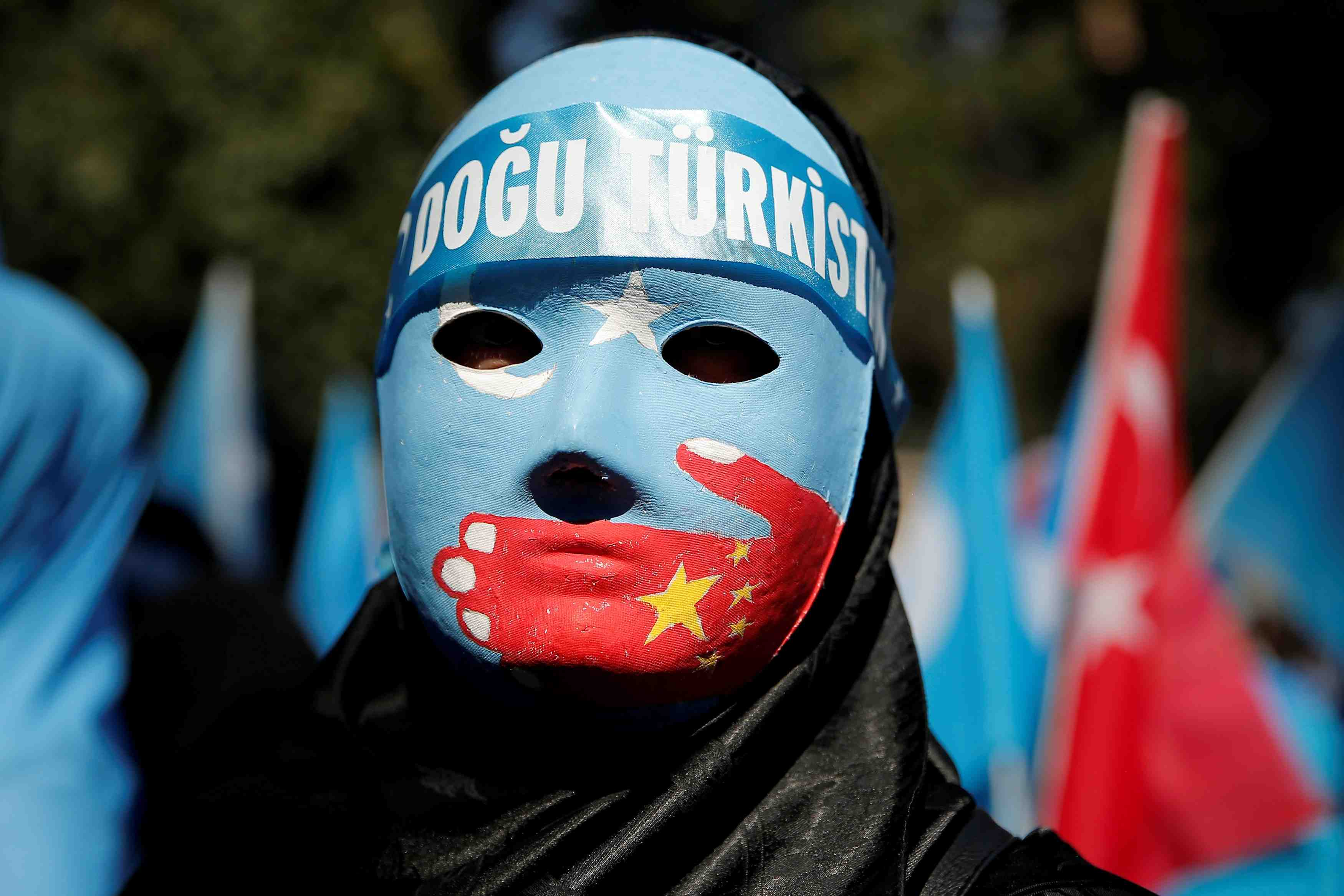 File Photo: Ethnic Uighur demonstrator wears a mask as she attends a protest against China in front of the Chinese Consulate in Istanbul