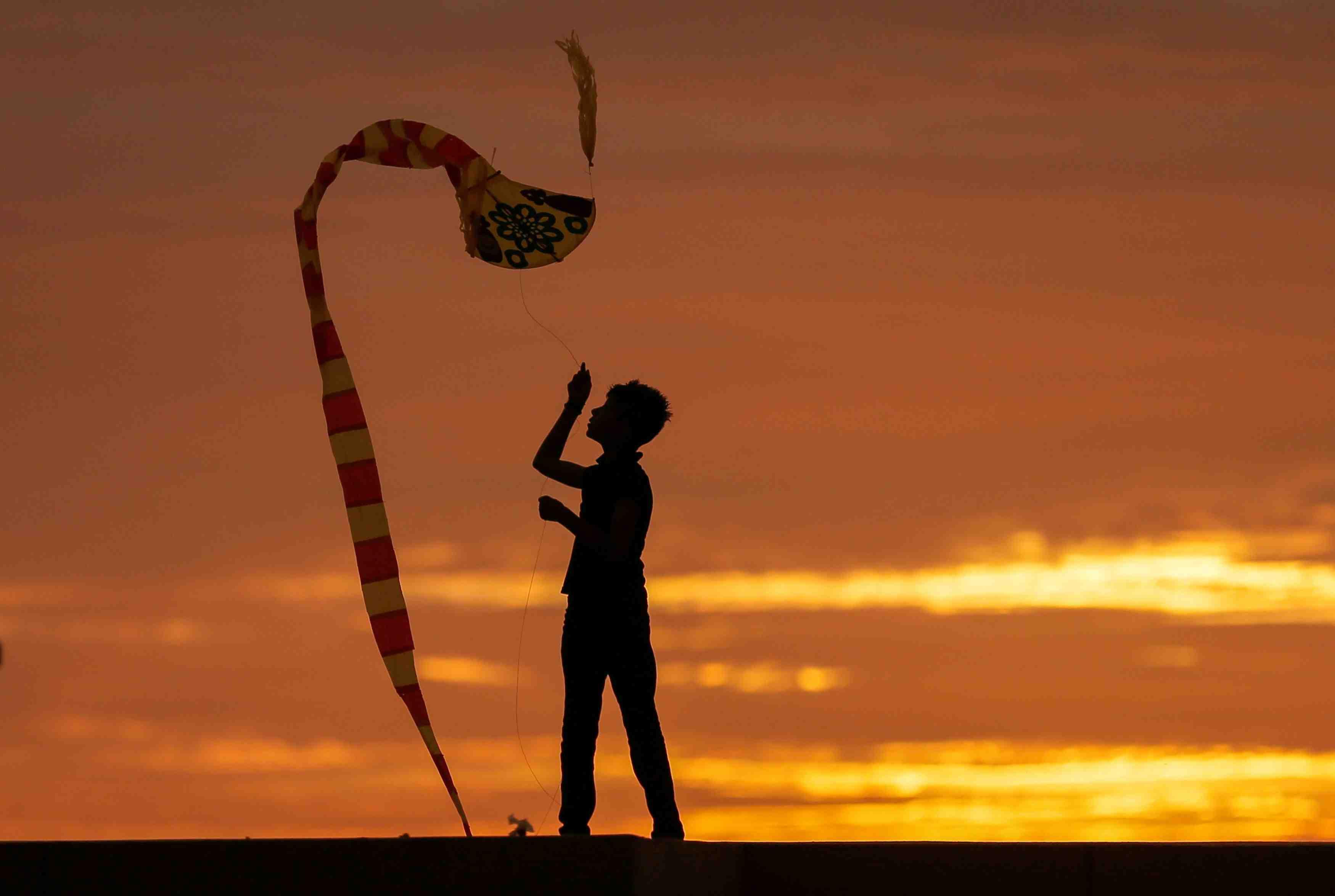 A boy is seen in silhouette as he flies a kite in Colombo