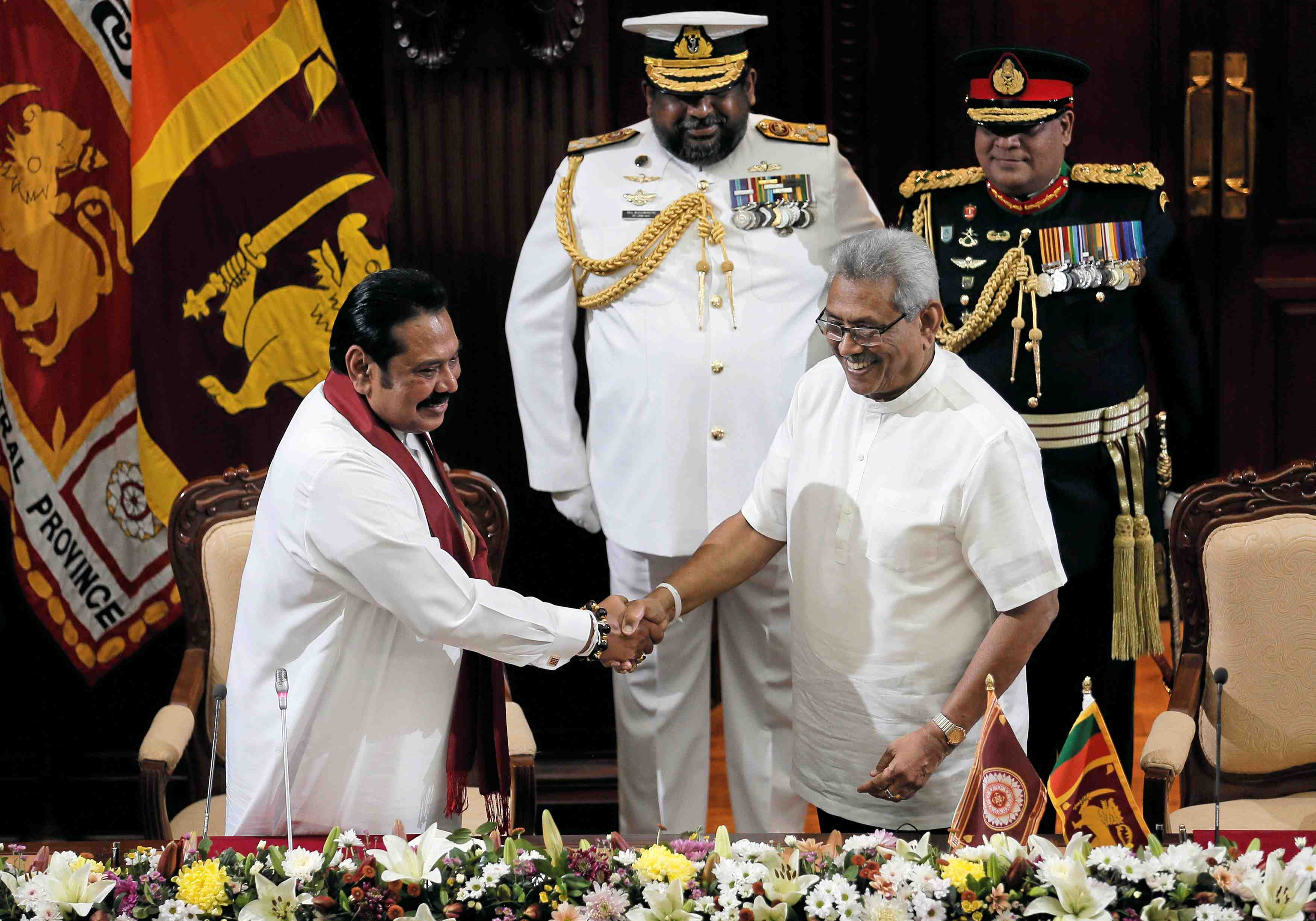 Sri Lanka's President Gotabaya Rajapaksa and his brother and former leader Mahinda Rajapaksa, who has appointed as the new Prime Minister, shake hands during the swearing in ceremony in Colombo