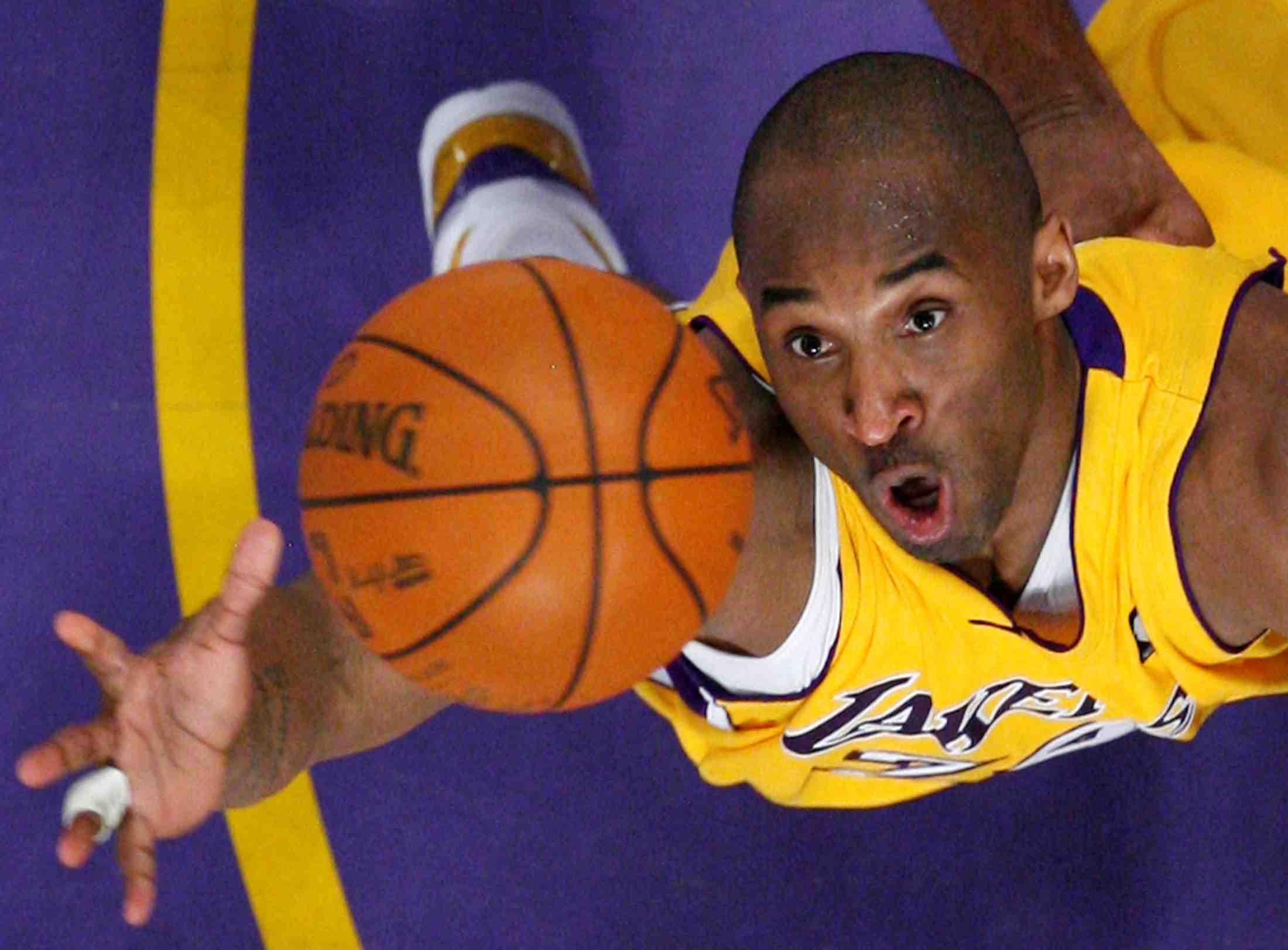 FILE PHOTO: Los Angeles Lakers Bryant jumps for a rebound against the Denver Nuggets during NBA Western Conference final basketball playoff game in Los Angeles