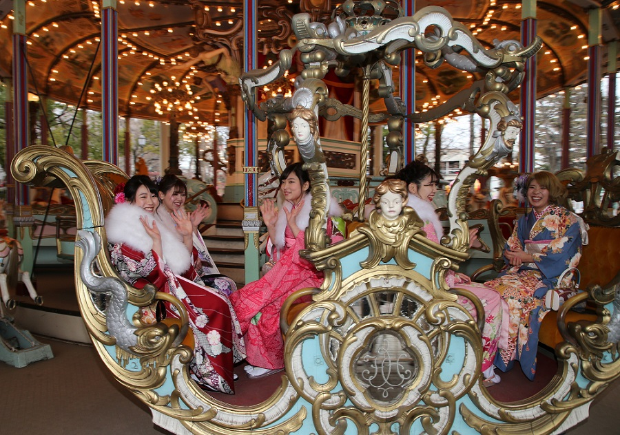 Japanese coming-of-age ladies riding on a merry-go round in Toshimaen