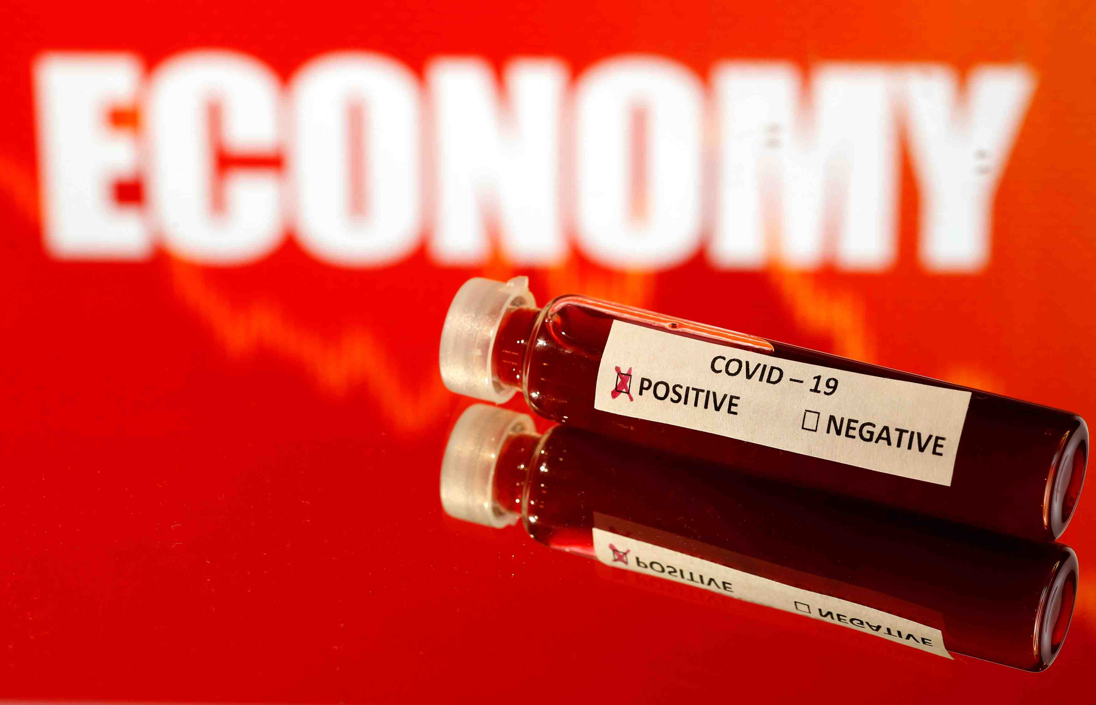 "Fake blood is seen in a test tube labelled with the coronavirus (COVID-19) in front of the word ""Economy"" in this illustration"