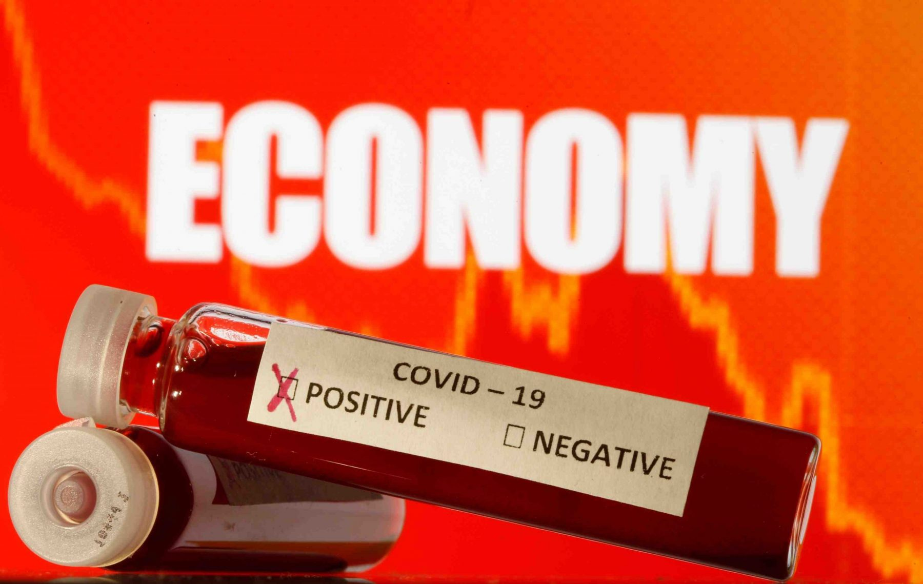 """Fake blood is seen in test tubes labelled with the coronavirus (COVID-19) in front of the word """"Economy"""
