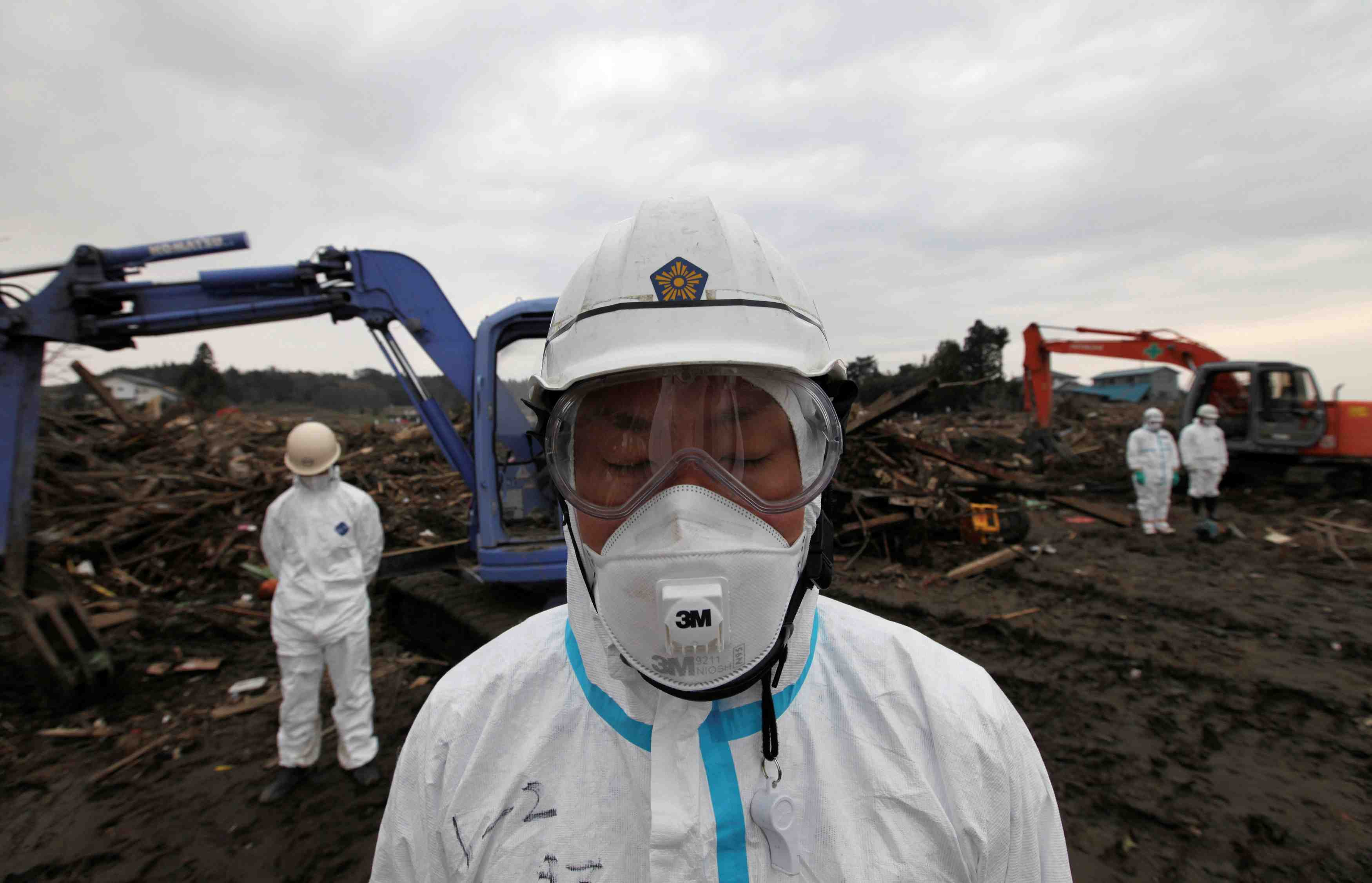 FILE PHOTO: Police officers in protective suits observe a moment of silence for those who were killed by the March 11 earthquake and tsunami, as they search for bodies at a destroyed area in Minamisoma, Fukushima prefecture