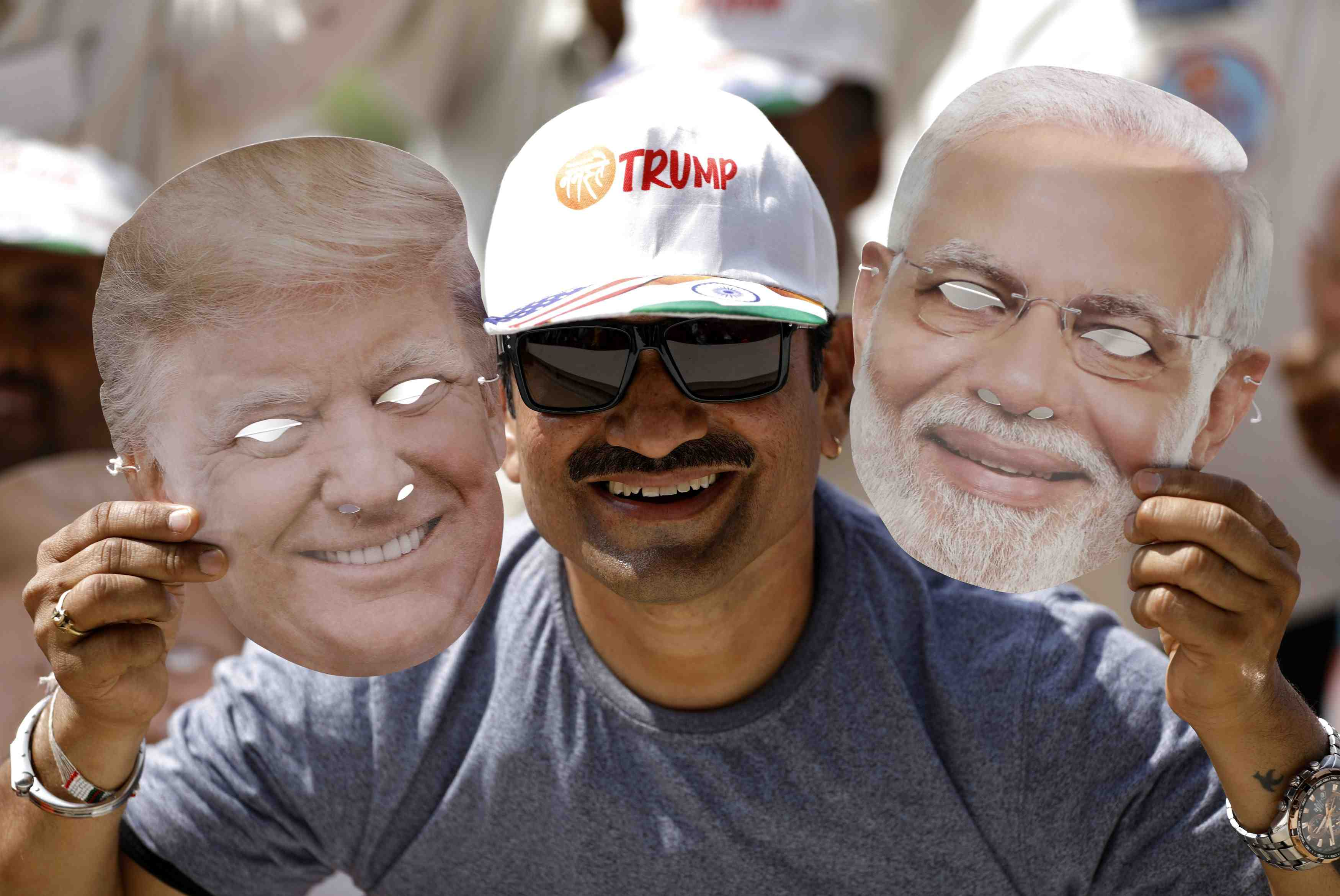 "A man holds masks depicting U.S. President Donald Trump and Indian Prime Minister Narendra Modi during the ""Namaste Trump"" event attended by Trump and Modi at Sardar Patel Gujarat Stadium, in Ahmedabad"