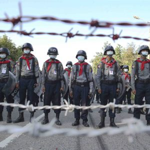 Police stand guard behind barbed wire as they attempt to stop protesters outside Union Election Commission office, Wednesday, Nov. 11, 2020, in Naypyitaw, Myanmar. The military backed main opposition party on Wednesday said it does not recognize last Sunday's Myanmar election, citing unfairness, and rejected the results. (AP Photo/Aung Shine Oo)